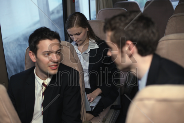 businessmen talking to each other, businesswoman using laptop stock photo