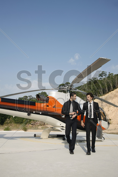 businessmen walking away from helicopter stock photo