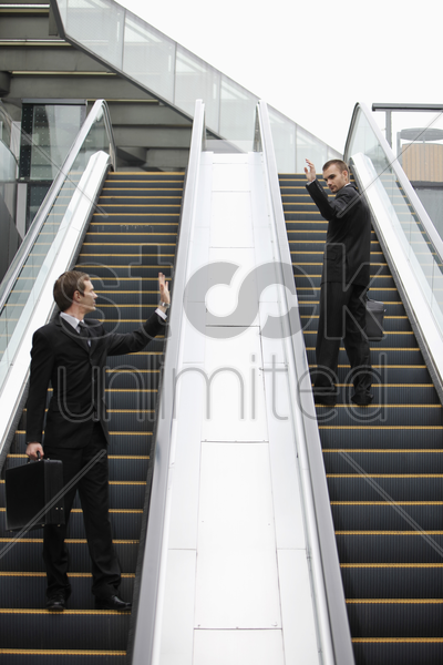 businessmen waving at each other on escalator stock photo
