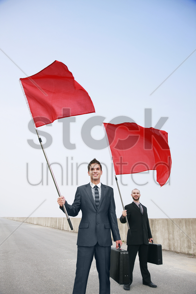 businessmen with bags and red flags stock photo