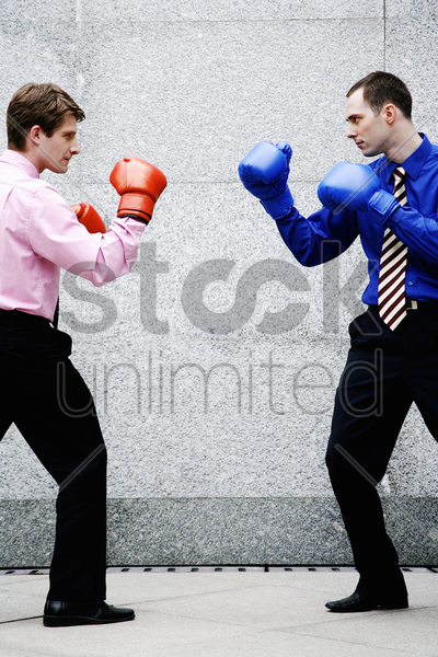businessmen with boxing gloves getting ready to fight stock photo