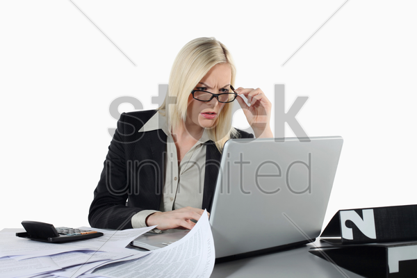businesswoman adjusting glasses while using laptop stock photo