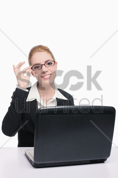businesswoman adjusting her glasses while using laptop stock photo