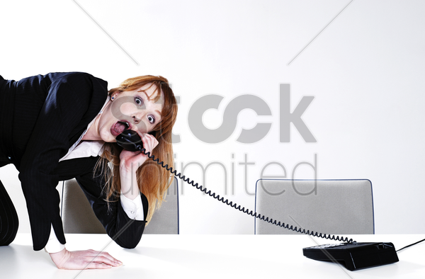 businesswoman answering call in an uncomfortable way stock photo