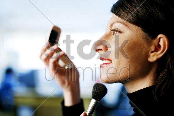 businesswoman applying makeup stock photo