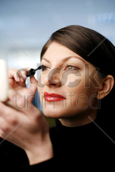 businesswoman applying mascara stock photo