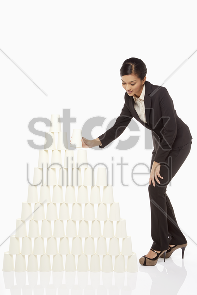 businesswoman arranging disposable cups stock photo