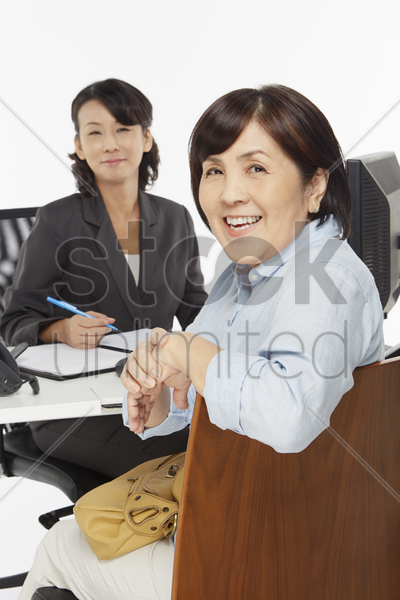 businesswoman attending to a customer stock photo