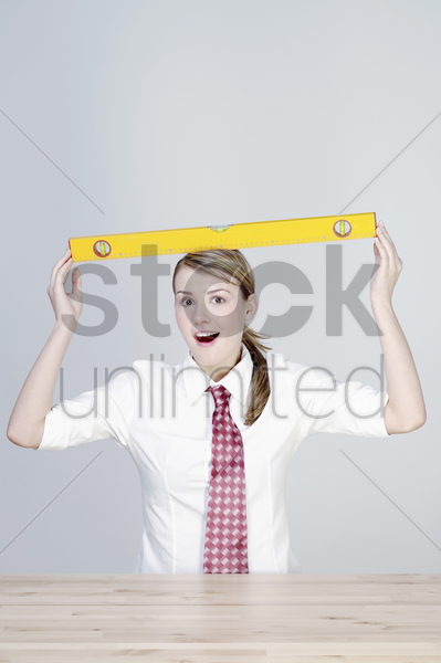 businesswoman balancing a spirit level on her head stock photo