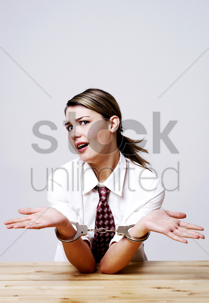 businesswoman being handcuffed stock photo