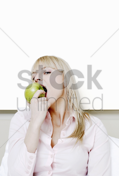 businesswoman biting a green apple stock photo