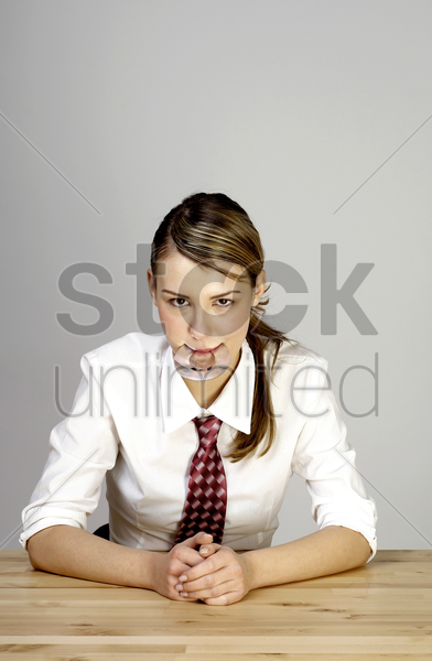 businesswoman biting a teether stock photo