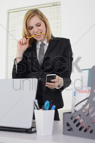 businesswoman biting on pencil while reading text message on phone stock photo