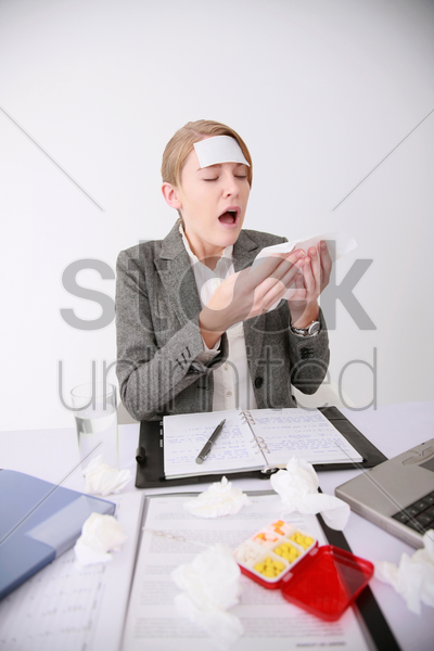 businesswoman blowing her nose with tissue stock photo