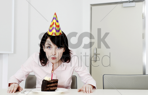 businesswoman blowing the candle on her birthday cake stock photo