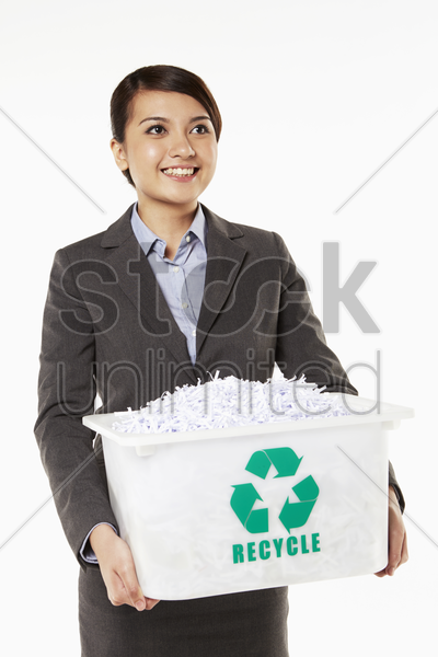 businesswoman carrying a box filled with shredded paper stock photo