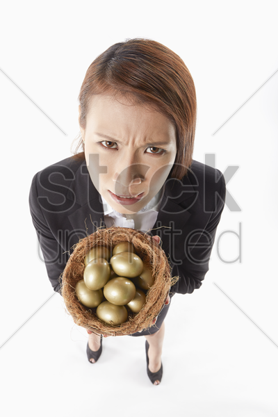 businesswoman carrying a nest filled with gold eggs stock photo