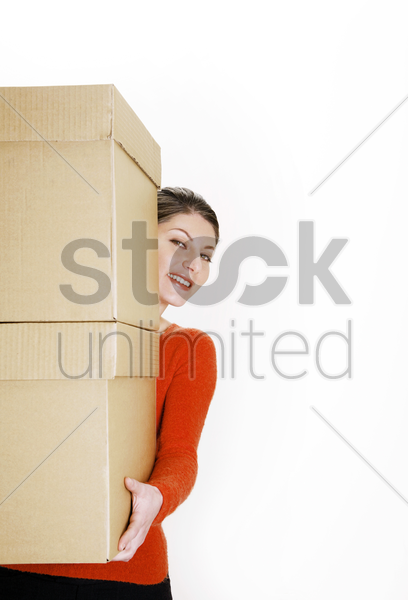 businesswoman carrying a stack of boxes stock photo