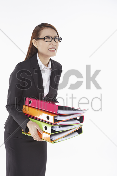 businesswoman carrying a stack of files stock photo
