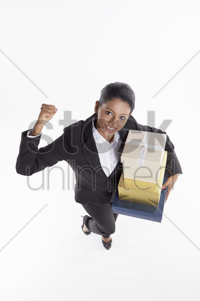 businesswoman carrying a stack of gift boxes and cheering stock photo