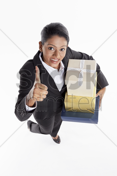 businesswoman carrying a stack of gift boxes and giving thumbs up stock photo