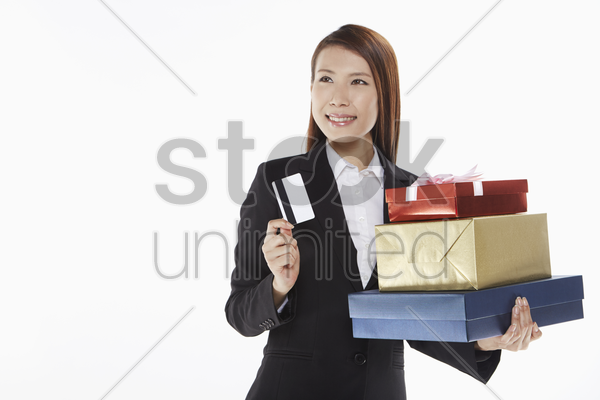 businesswoman carrying a stack of gift boxes and holding a credit card stock photo