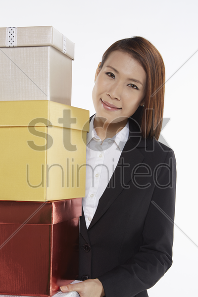 businesswoman carrying a stack of gift boxes stock photo
