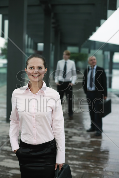 businesswoman carrying bag, businessmen in the background stock photo