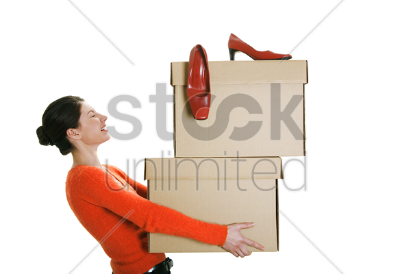 businesswoman carrying boxes with her high heels on top stock photo
