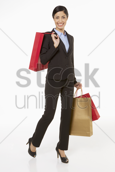 businesswoman carrying shopping bags stock photo