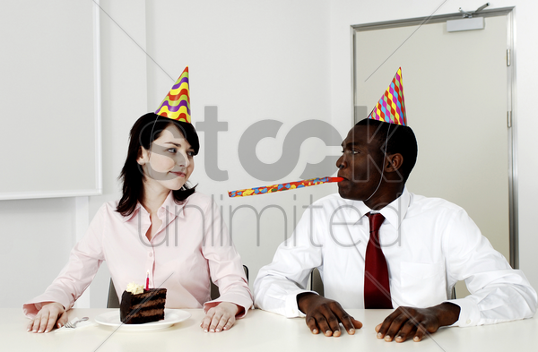 businesswoman celebrating her birthday with a colleague stock photo