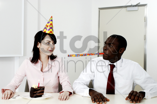businesswoman celebrating her birthday with a male colleague stock photo