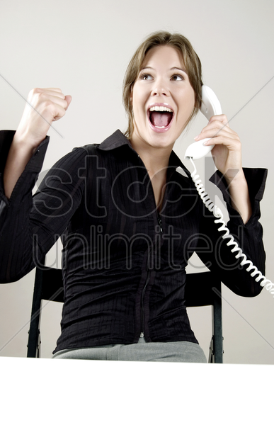 businesswoman celebrating while talking on the phone stock photo