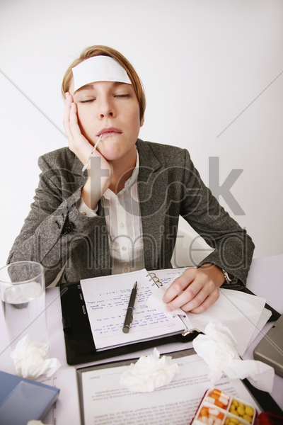 businesswoman checking her temperature with thermometer stock photo