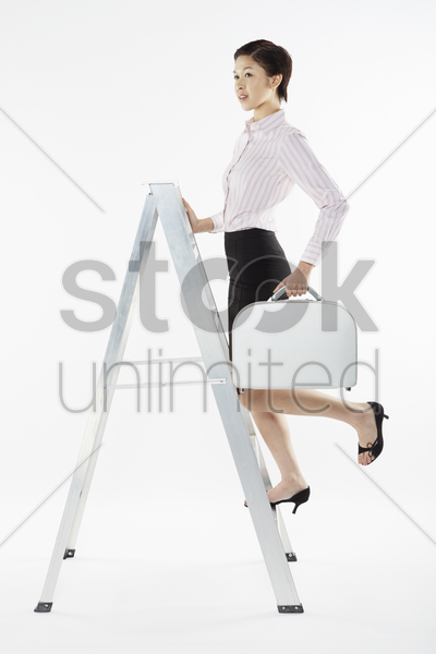 businesswoman climbing up a ladder while carrying briefcase stock photo