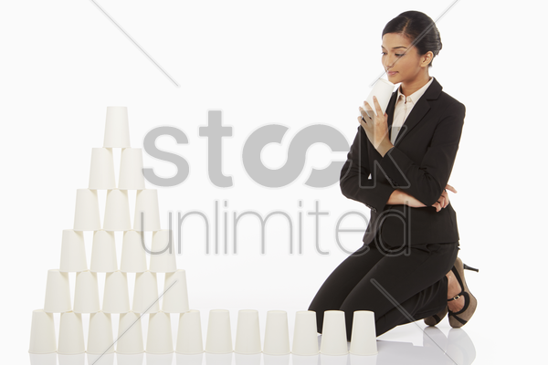 businesswoman contemplating while arranging disposable cups stock photo