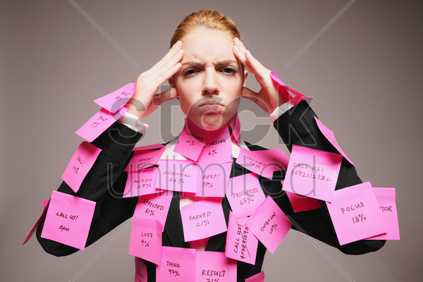 businesswoman covered with adhesive notes having headache stock photo