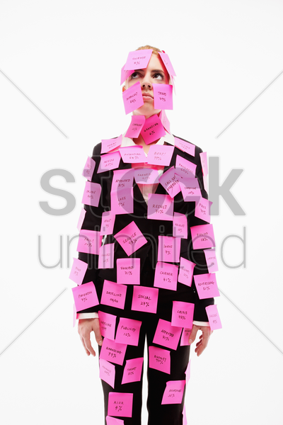 businesswoman covered with adhesive notes looking up and thinking stock photo