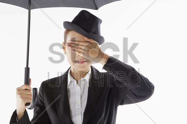 businesswoman covering her eyes while standing under the umbrella stock photo