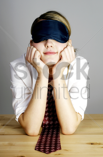 businesswoman covering her eyes with an eye mask stock photo