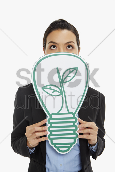 businesswoman covering her mouth with a cut out light bulb stock photo