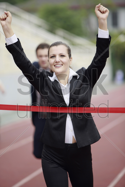 businesswoman crossing the finishing line stock photo