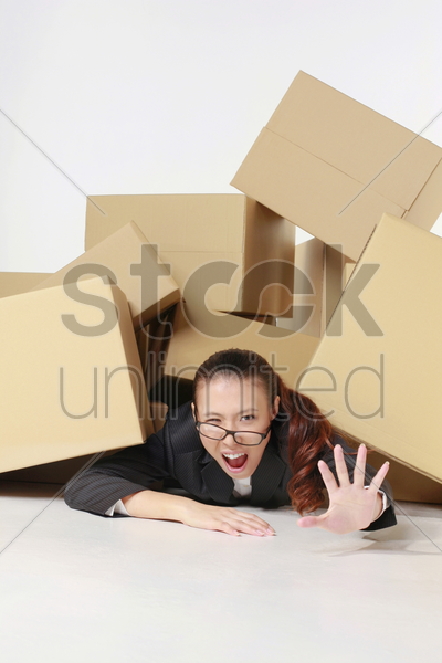 businesswoman crying for help while being buried under a pile of boxes stock photo