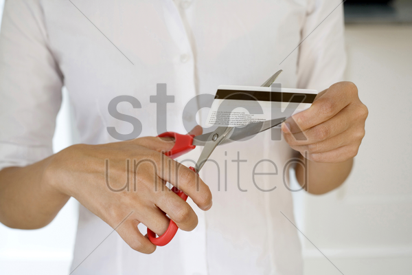 businesswoman cutting credit card stock photo