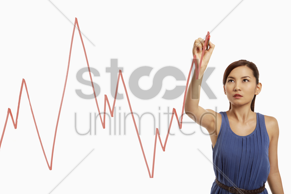 businesswoman drawing graph chart on a glass stock photo