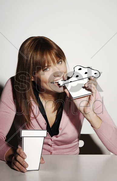 businesswoman eating cardboard cut-out cake stock photo