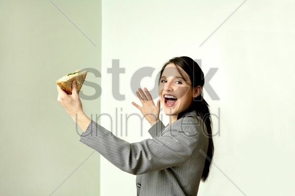 businesswoman eating sandwich stock photo