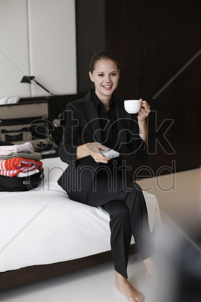 businesswoman enjoying a cup of coffee with remote control in hand stock photo
