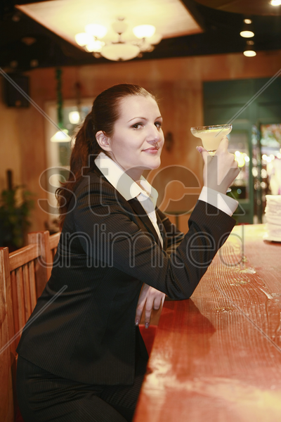 businesswoman enjoying a glass of cocktail stock photo