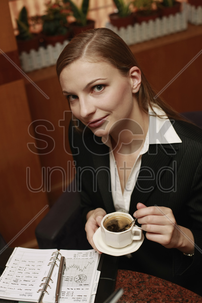 businesswoman enjoying coffee at cafe stock photo